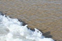 Onda espumosa na praia Foto de Stock
