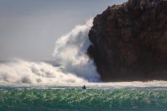 Onda gigante que se estrella en rocas cerca de una persona que practica surf Imagen de archivo libre de regalías