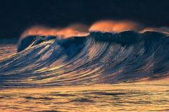 Onda grande sola que se rompe en la puesta del sol imagen de archivo
