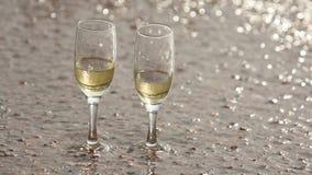 A onda lavou afastado um de dois vidros do champanhe, estando na areia na praia filme