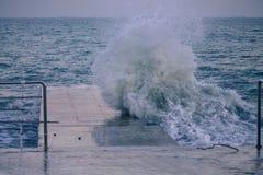 Onda poderosa do respingo do mar no cais fotografia de stock royalty free