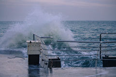 Onda poderosa do respingo do mar no cais fotos de stock royalty free