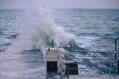 Onda poderosa do respingo do mar no cais imagens de stock royalty free