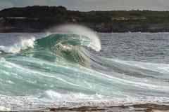 Onda potente de la resaca que se estrella en la playa Imagenes de archivo