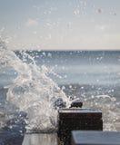 Onda que salpica sobre rompeolas en la playa Fotos de archivo