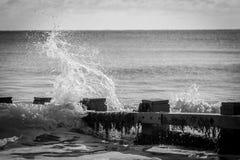 Onda que se estrella contra rompeolas en bahía Fotografía de archivo