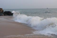 Onda que se estrella en el rocoso y la playa Imagen de archivo