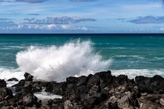 Onda que se rompe en roca negra de la lava en Hawaii Espray blanco en el aire Océano, cielo azul y nubes en fondo imágenes de archivo libres de regalías