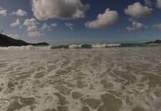 Onda spumosa della spiaggia con i cieli blu Immagine Stock