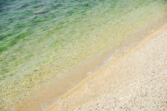 Onda suave del mar en una arena y un Pebble Beach Fotografía de archivo libre de regalías