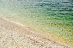 Onda suave del mar en una playa arenosa y un Pebble Beach Imágenes de archivo libres de regalías