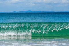 Onda verde esmeralda que se rompe en la playa de la bahía de la aventura imagen de archivo