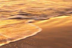 Onda y arena en la puesta del sol Imagen de archivo libre de regalías