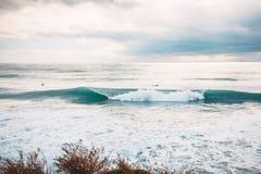 Onda y personas que practica surf de fractura perfectas del barril del océano Foto de archivo libre de regalías