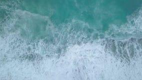 Ondas aéreas do mar da vista superior que espumam e que espirram de cima do rolamento e da quebra na praia vazia do oceano vídeos de arquivo