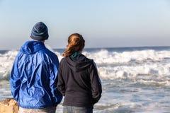 Ondas adolescentes de la playa de la muchacha del muchacho Imagenes de archivo