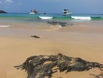 Ondas, barcos y roca negra fotografía de archivo libre de regalías