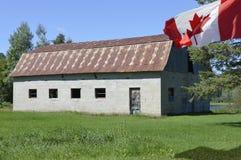 Ondas canadenses de uma bandeira na brisa ao lado de um celeiro abandonded velho fotos de stock