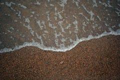 Ondas con espuma contra la perspectiva de ondas de arena con espuma contra la perspectiva de la arena Imagen de archivo