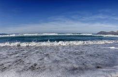 Ondas con espuma en una playa Fotos de archivo