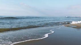 Ondas con la espuma en el color verde de mar, playa arenosa larga metrajes