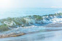 Ondas con un tinte verde en la playa imagenes de archivo
