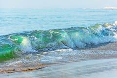 Ondas con un tinte verde en la playa foto de archivo libre de regalías