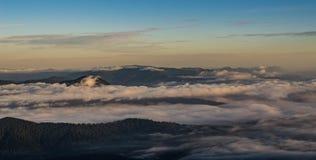 Ondas das nuvens que rolam sobre as montanhas Fotos de Stock Royalty Free