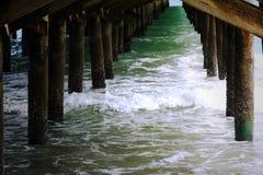 Ondas de água do oceano sob o cais imagem de stock