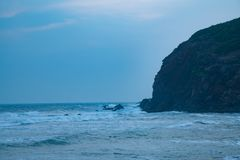 Ondas de água na praia que bate a névoa da montanha fotos de stock royalty free