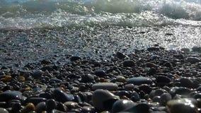 Ondas de agua puras en piedras y guijarros pulidos multicolores almacen de metraje de vídeo