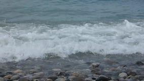 Ondas de agua puras que mueven encendido piedras pulidas multicoloras metrajes