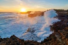 Ondas de asalto del mar que se estrellan en la orilla en la puesta del sol imagenes de archivo