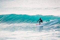 Ondas de la persona que practica surf y del azul Invierno que practica surf en el océano Imagen de archivo