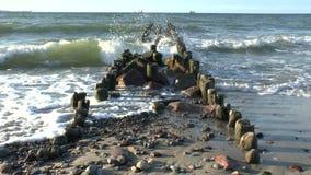 Ondas de la rotura del mar Báltico en un rompeolas de madera viejo metrajes