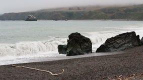 Ondas de oceano contra a rocha na praia com céu nublado vídeos de arquivo