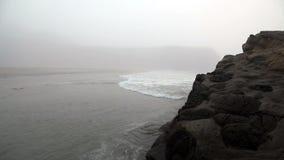 Ondas de oceano delicadas em torno da grande rocha encoberta na névoa filme