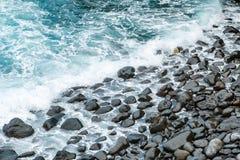 Ondas de oceano na costa preta da pedra do seixo imagens de stock