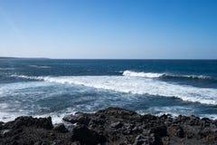 Ondas de oceano no litoral rochoso preto imagens de stock
