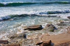 Ondas de Oceano Pacífico em rochas da praia de Cronulla e em areia, Sydney, Austrália imagem de stock