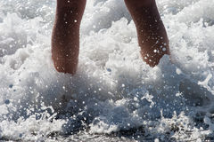 Ondas de oceano que espirram sobre os pés da criança fotos de stock