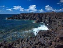 Ondas de oceano que quebram na costa rochosa da lava endurecida com cavernas e cavidades Céu azul profundo com nuvens e as montan fotos de stock