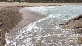 Ondas de relajación que se lavan sobre la playa metrajes