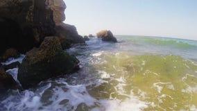Ondas del mar después de un incidente de la tormenta en la orilla y de estrellarse en las rocas almacen de video