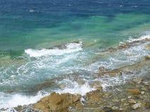 Ondas del Mar Egeo de los azules turquesa que se estrella en las rocas en Mykonos imagenes de archivo