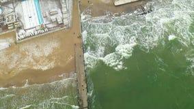 Ondas del mar que se estrellan en el embarcadero concreto Silueta del hombre de negocios Cowering Odessa, Ucrania, enero de 2019 almacen de video