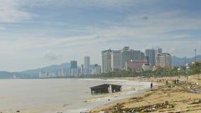 Ondas del reloj de los hombres que lavan la casa arruinada por la playa después de tifón
