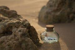 Ondas do farol e de oceano dentro da garrafa que está na areia entre as rochas Fotos de Stock