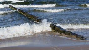 Ondas do mar com quebra-mar de madeira e Sandy Beach limpo imagens de stock royalty free