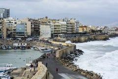 Ondas e baía fortes com os navios no fundo da cidade e das montanhas em Grécia imagem de stock